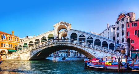 VENICE - DECEMBER 12: Rialto Bridge (Ponte Di Rialto) on a sunny day with tourists on December 12, 2012 in Venice. Its oldest and one of the four bridges spanning the Grand Canal in Venice. Editorial