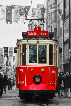 tramcar: ISTANBUL - APRIL 9: Old-fashioned red tram at the street with pedestrians in Istanbul on April 09, 2013. Nostalgic tram of Istanbul is the heritage tramway system. It was re-established in 1990 and gained much popularity mainly among the tourists.
