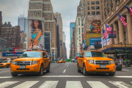 among: NEW YORK CITY - MAY 12: Yellow taxis at the street on May 12, 2013 in New York. Yellow cars serve as taxis in NYC and are easy to spot among other vehicles because of their color.