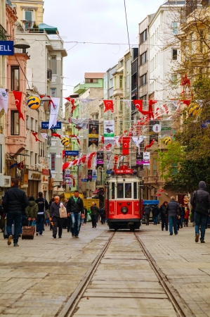 tramcar: ISTANBUL - APRIL 9: Old-fashioned red tram at the street with pedestrians in Istanbul on April 07, 2013. Nostalgic tram of Istanbul is the heritage tramway system. It was re-established in 1990 and gained much popularity mainly among the tourists.