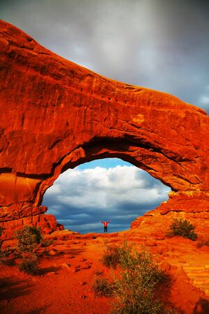 Woman staying with raised hands inside an Arch at the Arches National Park, UT photo
