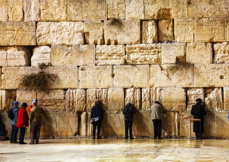 JERUSALEM - DECEMBER 15: The Western Wall in the night with a praying pilgrims on December 15, 2013 in Jerusalem. Its located in the Old City of Jerusalem at the foot of the western side of the Temple Mount. Editorial
