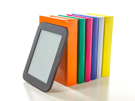 Electronic book reader with a row of hard cover books photo