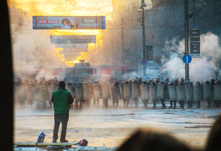 anti season: KIEV, UKRAINE - JANUARY 24  A row of the riot police with a priest at Hrushevskogo street on January 24, 2014 in Kiev, Ukraine  The anti-governmental protests were provoked when the Ukrainian president denied to sign an agreement with the EU  Editorial