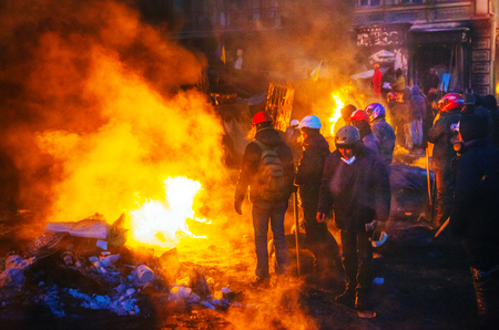 provoked: KIEV, UKRAINE - JANUARY 24  Barricade with the protesters at Hrushevskogo street on January 24, 2014 in Kiev, Ukraine  The anti-governmental protests were provoked when the Ukrainian president denied to sign an agreement with the EU