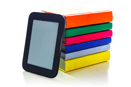 Electronic book reader with a pile of hard cover books