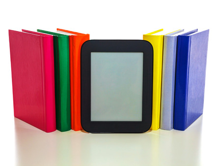 Electronic book reader with a row of hard cover books Stock Photo