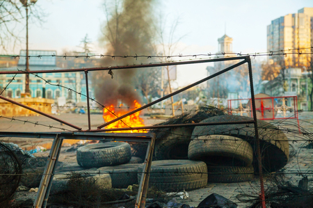 provoked: KIEV, UKRAINE - FEBRUARY 20: Burning tires at the barricade during the revolution on February 20, 2014 in Kiev, Ukraine. The anti-governmental protests were provoked when the Ukrainian president denied to sign an agreement with the EU. Editorial