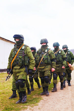 invade: PEREVALNE, UKRAINE - MARCH 5  Russian soldier marching on March 5, 2014 in Perevalne, Ukraine  On February 28, 2014 Russian military forces invaded Crimea peninsula
