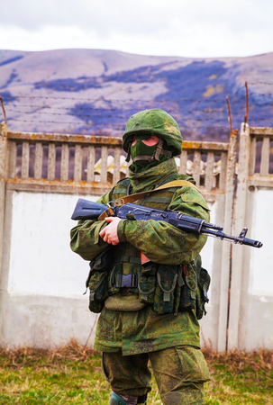 invade: PEREVALNE, UKRAINE - MARCH 5  Russian soldier guarding an Ukrainian naval base on March 5, 2014 in Perevalne, Crimea, Ukraine  On February 28, 2014 Russian military forces invaded Crimea peninsula