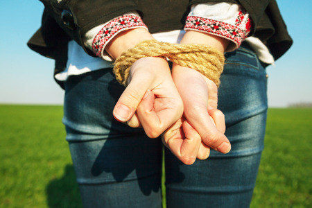 Female hands tied up with the rope photo