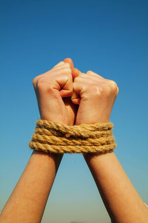 Hands tied up with rope against blue sky photo