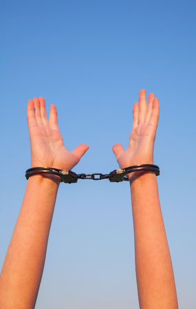 Handcuffed woman hands against blue sky photo