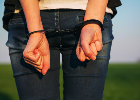 handcuffed hands: Woman with handcuffed hands outdoors