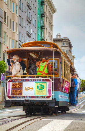 SAN FRANCISCO - APRIL 24: Famous cable car with people at a steep street on April 24, 2014 in San Francisco, California. The cable car system forms part of the intermodal urban transport network.