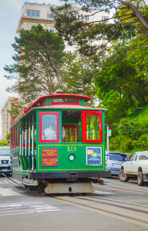 intermodal: SAN FRANCISCO - APRIL 24: Famous cable car with people at a steep street on April 24, 2014 in San Francisco, California. The cable car system forms part of the intermodal urban transport network.