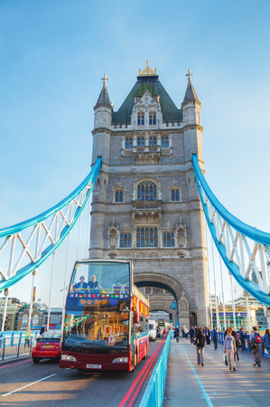 LONDON - APRIL 14: Tower bridge with a touristic double-decker bus on April 14, 2015 in London, UK. It (built 1886–1894) is a combined bascule and suspension bridge in London, England which crosses the River Thames. Redactioneel