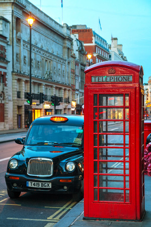 gilbert: LONDON - APRIL 12: Famous red telephone booth and taxi cab on April 12, 2015 in London, UK. The red telephone box, a telephone kiosk for a public telephone designed by Sir Giles Gilbert Scott.