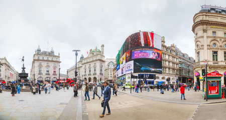 public space: LONDON - APRIL 13: Piccadilly Circus junction crowded by people on April 13, 2015 in London, UK. Its a road junction and public space of Londons West End in the City of Westminster, built in 1819.