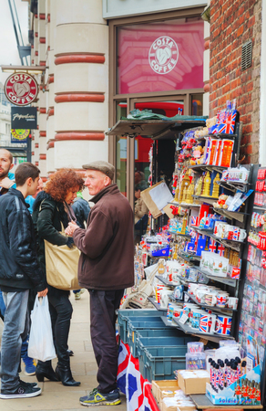 equivalent: LONDON - APRIL 13: Street souvenir shop with tourists on April 13, 2015 in London, UK. London is a popular centre for tourism, one of its prime industries, employing the equivalent of 350,000 full-time workers.