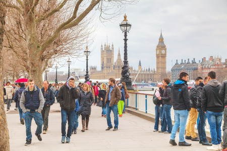 equivalent: LONDON - APRIL 4: Thames riverbank crowded with tourists on April 4, 2015 in London, UK. London is a popular centre for tourism, one of its prime industries, employing the equivalent of 350,000 full-time workers. Editorial