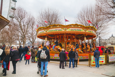 employing: LONDON - APRIL 4: Carousel at the Thames riverbank crowded with tourists on April 4, 2015 in London, UK. London is a popular centre for tourism, one of its prime industries, employing the equivalent of 350,000 full-time workers.