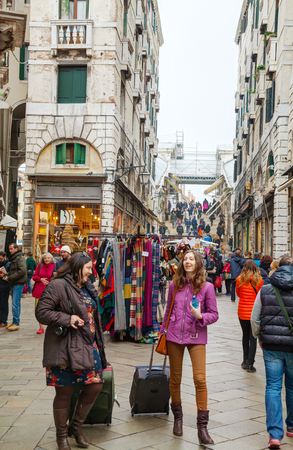 VENICE - NOVEMBER 20: Crowded with tourists street on November 20, 2015 in Venice, Italy. Venice is the capital of the Veneto region sited on a group of 118 small islands.