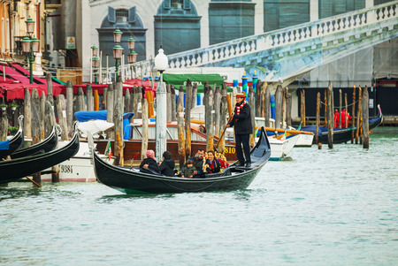 VENICE - NOVEMBER 22: Gondola with tourists on November 22, 2015 in Venice, Italy. The gondola is a traditional, flat-bottomed Venetian rowing boat, well suited to the conditions of the Venetian lagoon.