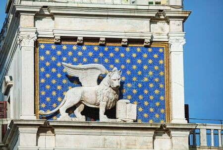 winged lion: Winged lion on facede of the bell tower at San Marco square in Venice, Italy Stock Photo