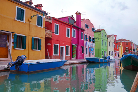 Burano: BURANO, ITALY - NOVEMBER 23: Brightly painted houses at the Burano canal on November 23, 2015 in Burano, Venice, Italy. Its an island in the Venetian Lagoon, northern Italy.