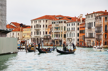 VENICE - NOVEMBER 22: Gondolas with tourists on November 22, 2015 in Venice, Italy. The gondola is a traditional, flat-bottomed Venetian rowing boat, well suited to the conditions of the Venetian lagoon.