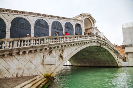rialto: VENICE - NOVEMBER 22: Rialto bridge (Ponte di Rialto) with tourists on November 22, 2015 in Venice, Italy. Its one of the four bridges spanning the Grand Canal.