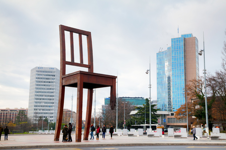 GENEVA, SWITZERLAND - NOVEMBER 28: Broken Chair monument near United Nations palace with tourists on November 28, 2015 in Geneva, Switzerland. Editorial