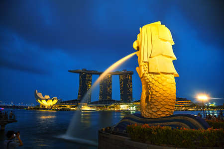 october 31: SINGAPORE - OCTOBER 31: Overview of the marina bay with the Merlion and Marina Bay Sands with people on October 31, 2015 in Singapore.