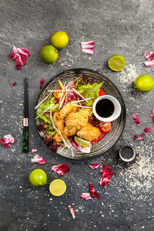 Traditional Japanese dish of fried chicken with vegetables and soya sauce on a black plate, view from the top