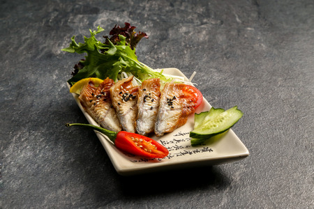 red  fish: Red fish on a white plate with lettuce leaves on a dark stone background Stock Photo