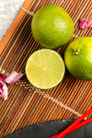 The fruit, which is added to food and beverages - lime green in a cut on a wooden mat