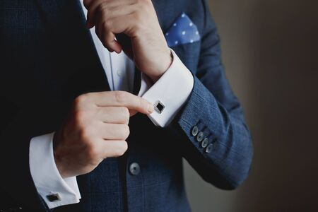 Close-up of a man in a tux fixing his cufflink. Stock Photo