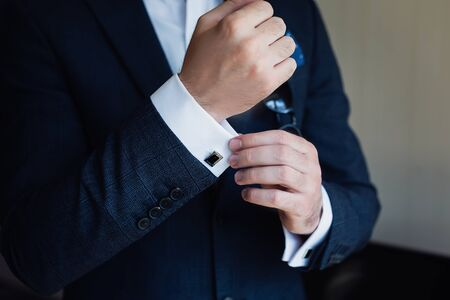 Close-up of a man in a tux fixing his cufflink. Stockfoto