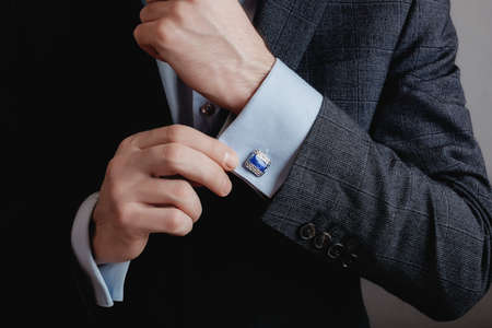 Close up of businessman wearing cufflinks. Elegant young fashion business man wearing suit. Stock Photo