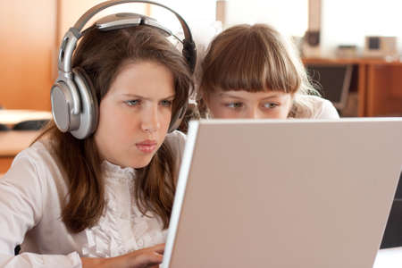 concentrated: Two schoolgirls concentrated on their task with notebook Stock Photo