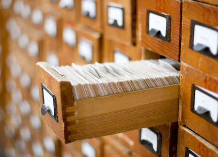 Old wooden card catalogue with one opened drawer photo