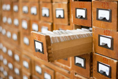 references: Old wooden card catalogue with one opened drawer