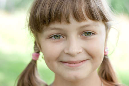 Fullface portrait of smiling little girl with green eyes and blond hair photo