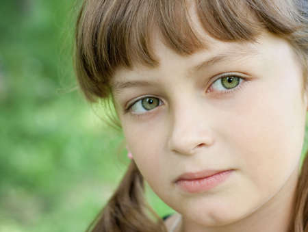 Fullface portrait of serious little girl with beautiful green eyes and blond hair photo