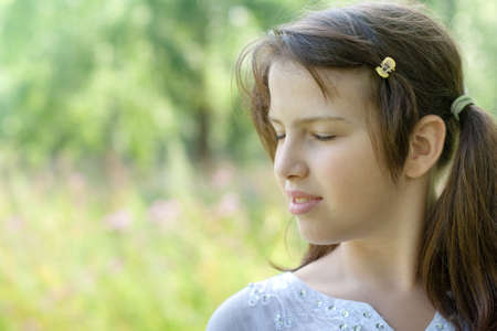 Portrait in profile of cute brunette girl standing outdoor  relaxing with closed eyes Stock Photo - 5814457