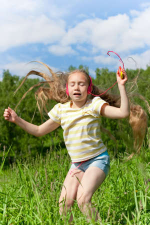 Blonde girl with closed eyes red earphones is listening mp3 player music and dancing photo