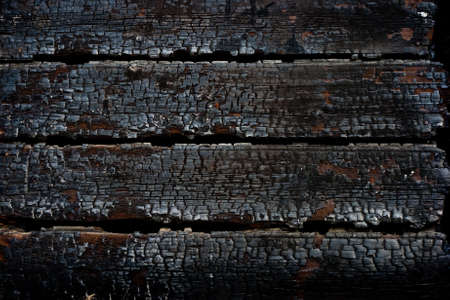 Closeup burned wooden wall after fire photo