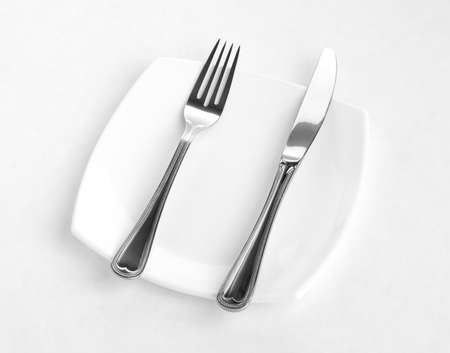 Place setting for one person. Knife, square white plate and fork. Stock Photo - 6021315