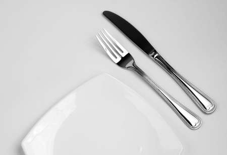 Place setting for one person. Knife, square white plate and fork. Stock Photo - 6021334